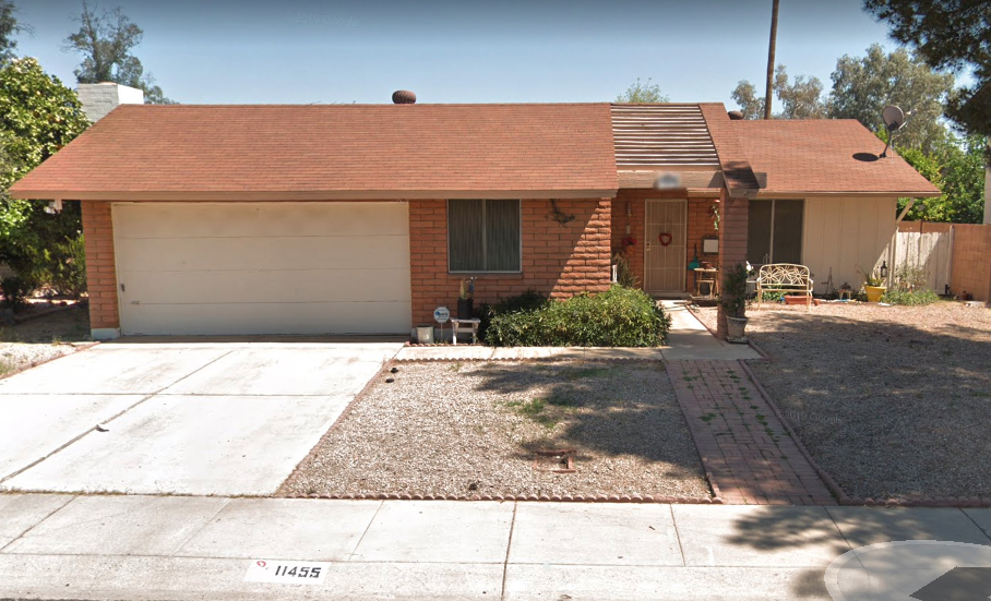 A house in suburban Phoenix with rocks in the front yard.