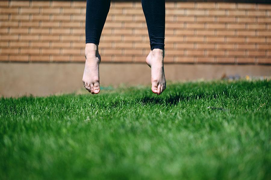 A pair of feet jumping off a lush, green lawn. Photo by Sharon McCutcheon.